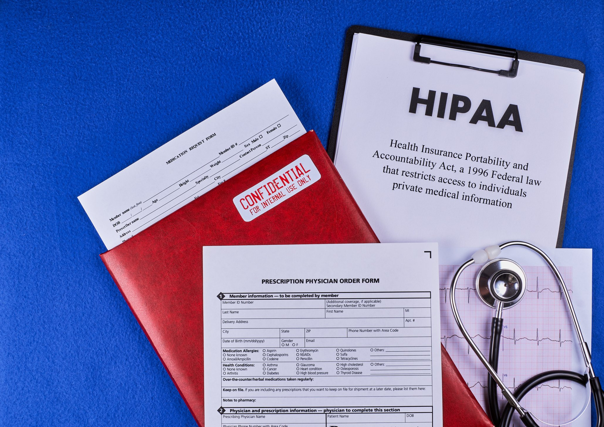 HIPAA paperwork and folders on a blue background with a stethoscope.
