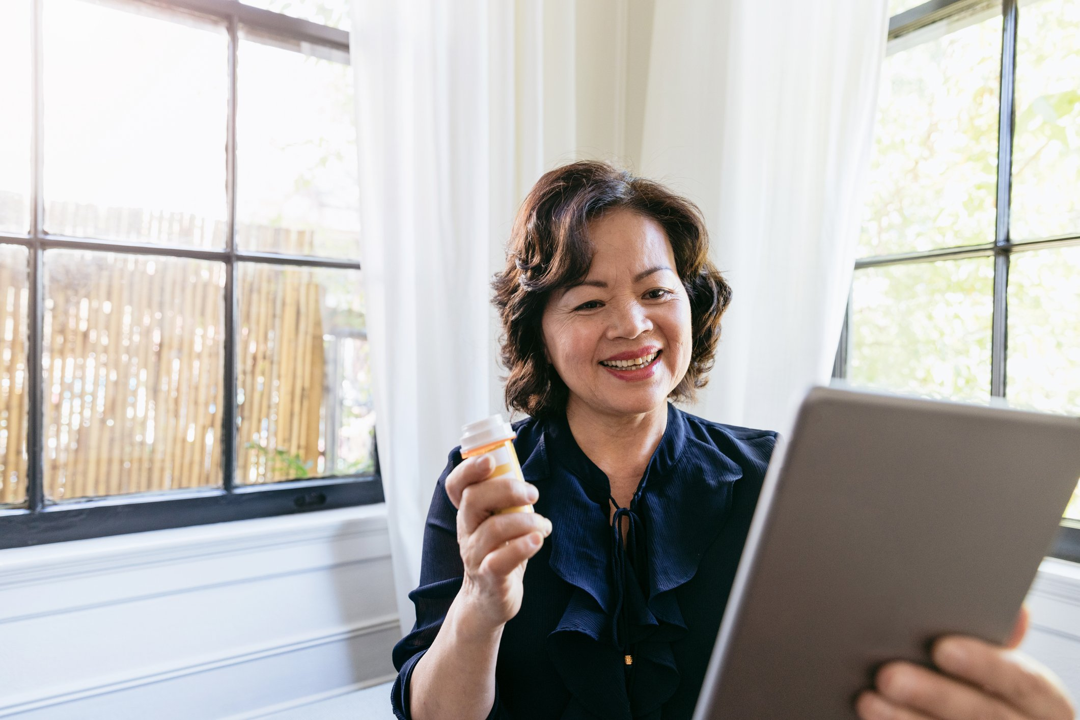 Older Asian woman holding a pill bottle and speaking with her doctor on a tablet using telemedicine technology